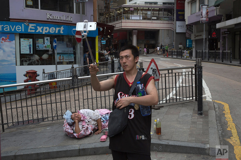 In this June 4, 2017, photo, a man takes a selfie with a homeless woman in Central district, Hong Kong. (AP Photo/Kin Cheung)