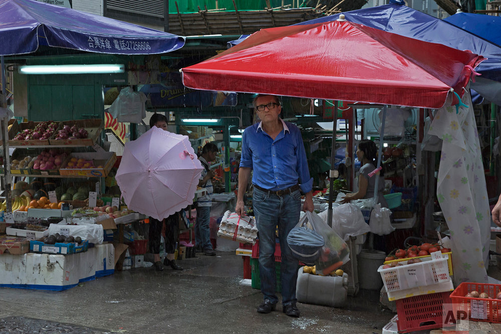 In this June 12, 2017, photo, a man takes shelter from a storm at a local market on the slope in Central district, Hong Kong. (AP Photo/Kin Cheung)