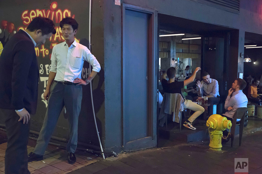 In this June 20, 2017, photo, men chat at a bar in Central district, Hong Kong. (AP Photo/Kin Cheung)