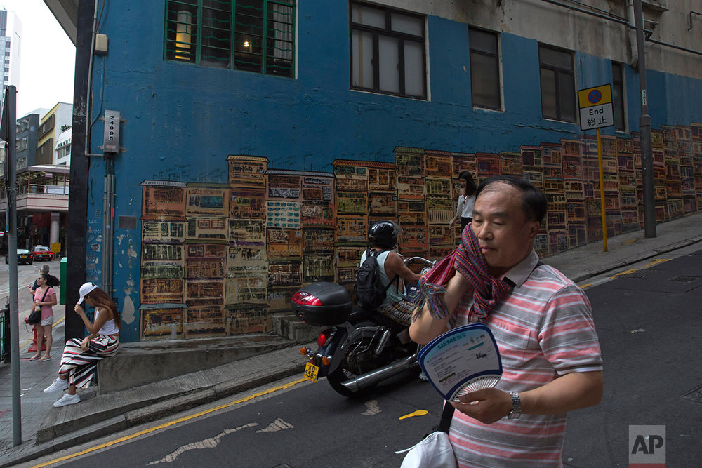 In this June 4, 2017, photo, a man walks down the slope in Central district, Hong Kong. (AP Photo/Kin Cheung)