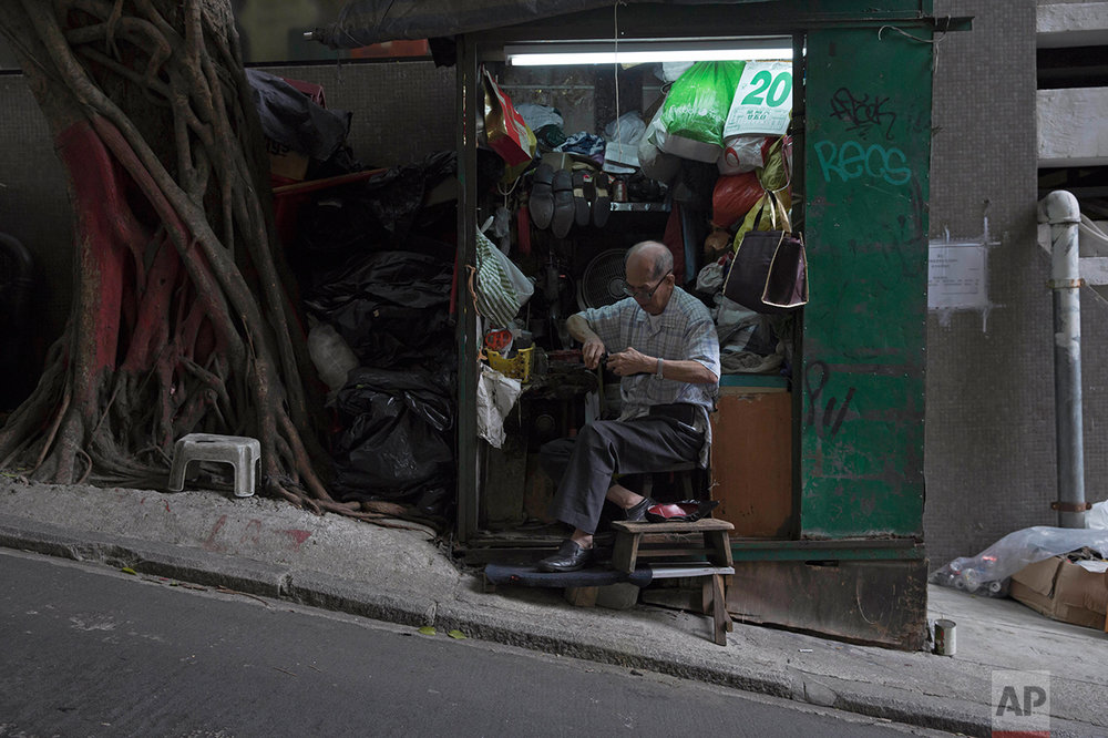In this May 20, 2017, photo, a man fixes shoes at his shop on the slope in Central district, Hong Kong. (AP Photo/Kin Cheung)