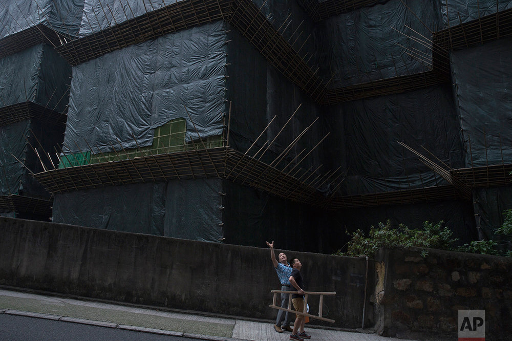 In this May 20, 2017, photo, two workers walk down the slope near a construction site in Central district, Hong Kong. (AP Photo/Kin Cheung)