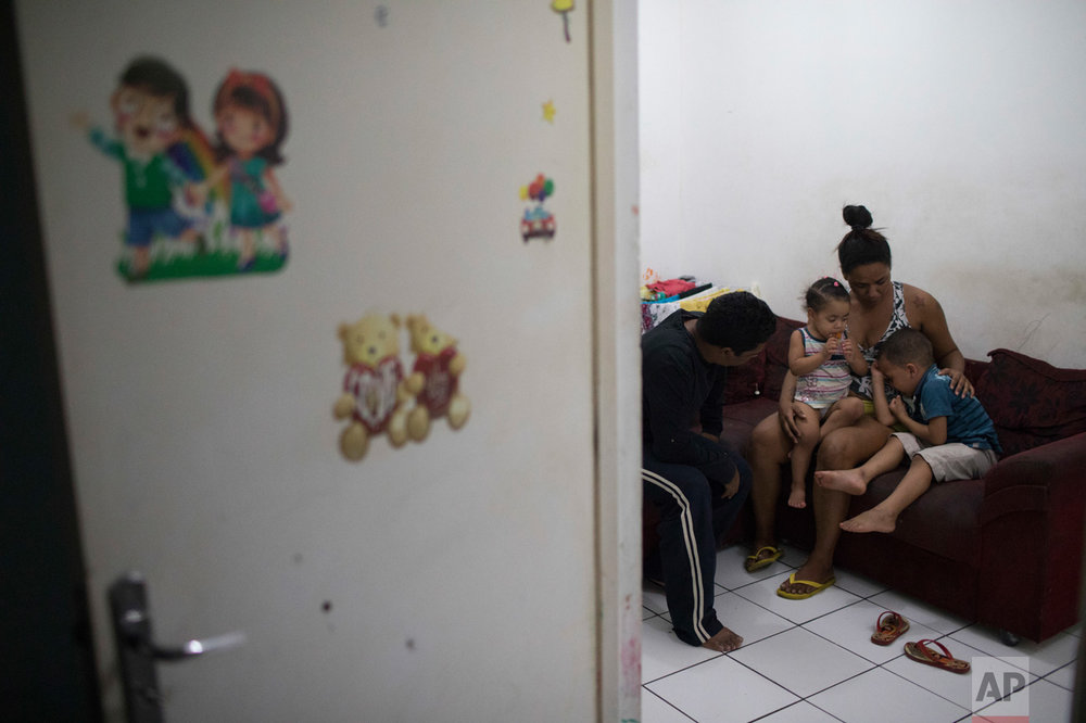 In this June 9, 2017 photo, Thaisa da Silva Ribeiro calms her four-year-old son Isaac, right, and two-year-old daughter Isadora as her husband Silvio Cesar Soares Gonzaga sits with them after a military police tank drove through their neighborhood in the City of God slum of Rio de Janeiro, Brazil. (AP Photo/Leo Correa)