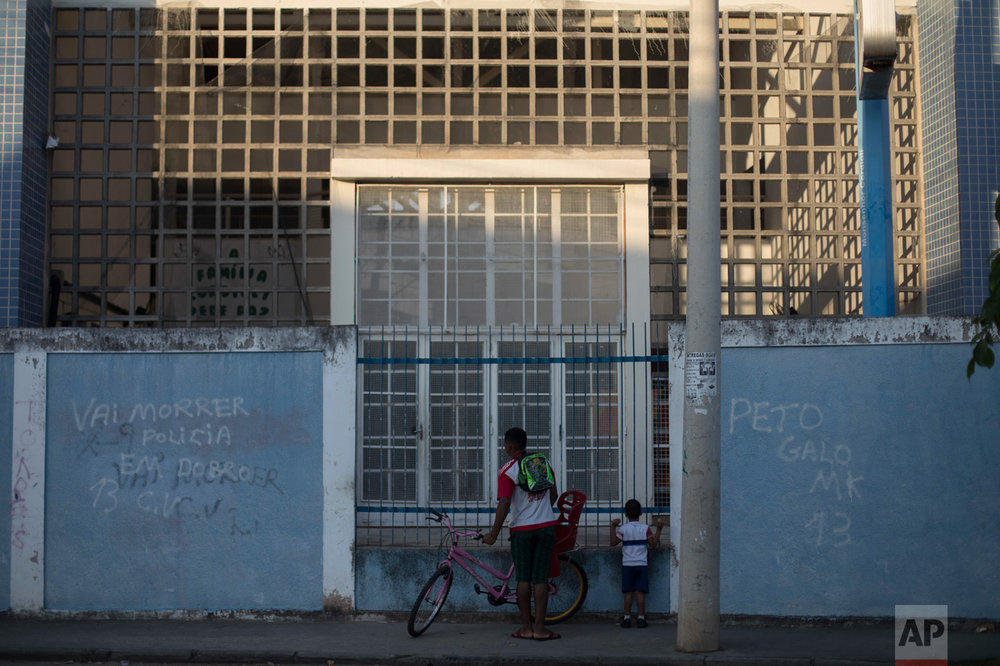 In this June 7, 2017 photo, a father waits for his son's gated school to open in the morning in the City of God slum of Rio de Janeiro, Brazil. (AP Photo/Leo Correa)