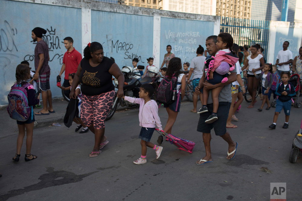 In this June 7, 2017 photo, Bruna Pedro, left, walks her daughter Kamylle to her school's entrance in the City of God slum of Rio de Janeiro, Brazil. (AP Photo/Leo Correa)