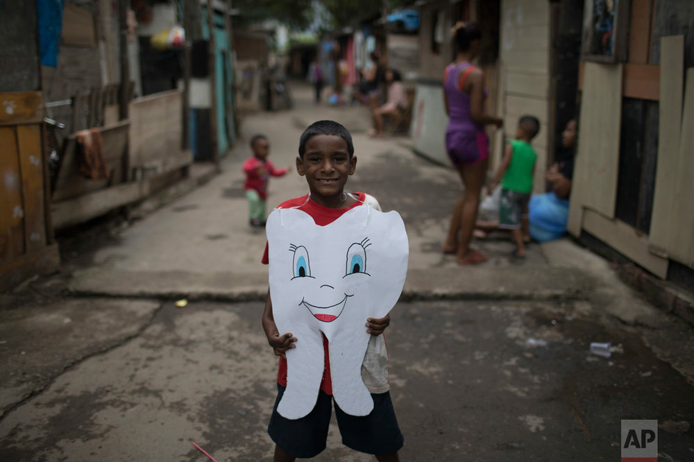 In this June 10, 2017 photo, a youth poses for the picture wearing a healthy tooth costume given to him by an NGO in one of the poorest area of the City of God slum in Rio de Janeiro, Brazil. (AP Photo/Leo Correa)