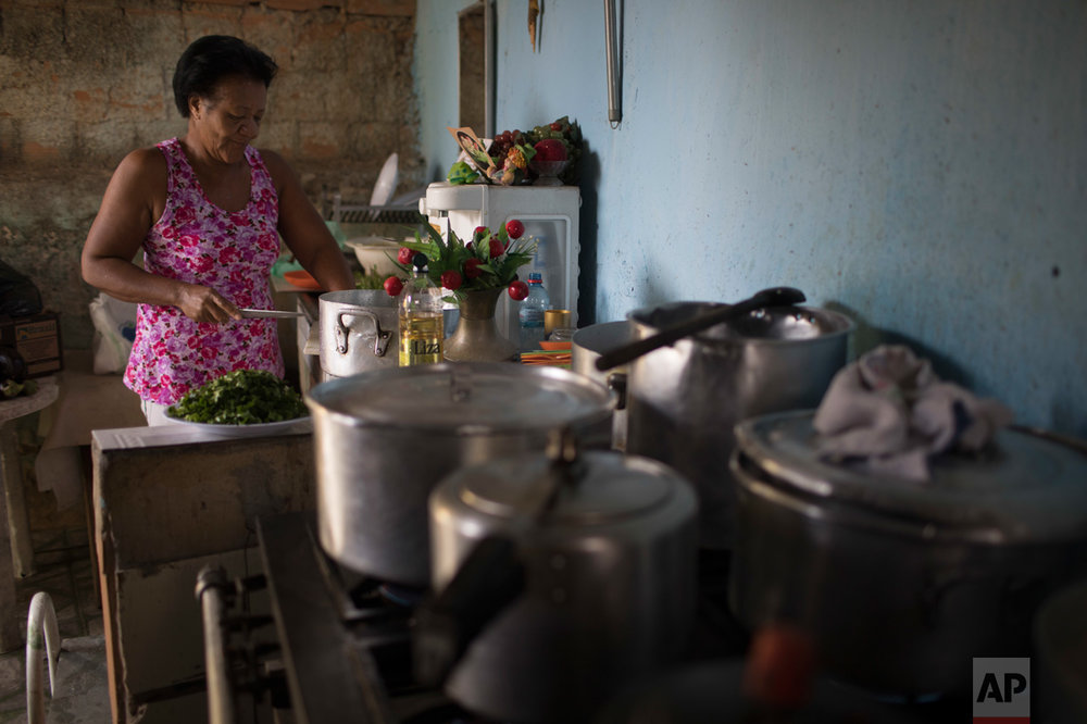 In this June 12, 2017 photo, Ana Regina de Jesus cooks in the City of God slum of Rio de Janeiro, Brazil. (AP Photo/Leo Correa)