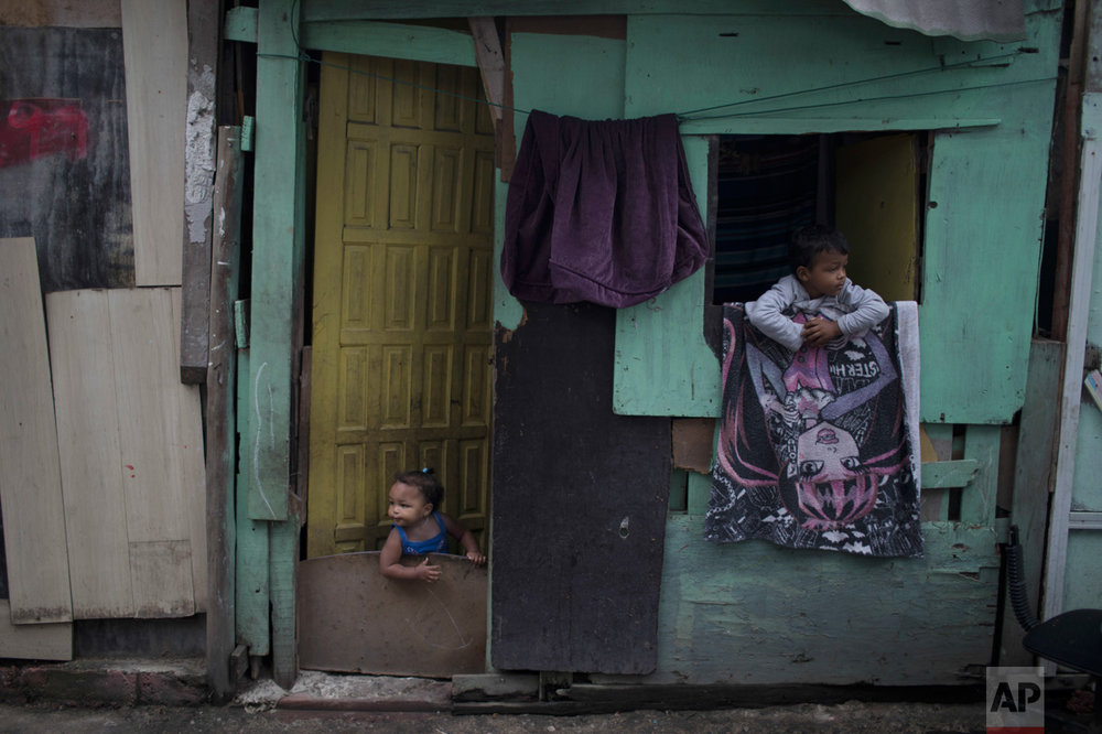 "In this June 10, 2017 photo, kids peer from their shack in the neighborhood of ""Cantinho do Ceu"" which means in Portuguese ""Heaven's corner,"" one of the poorest areas of City of God slum in Rio de Janeiro, Brazil. (AP Photo/Leo Correa)"