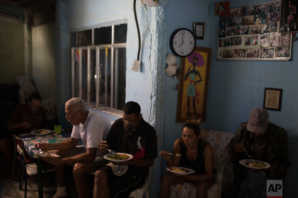 In this June 12, 2017 photo, people eat a free lunch inside the home of Ana Regina de Jesus in the City of God slum in Rio de Janeiro, Brazil. (AP Photo/Leo Correa)