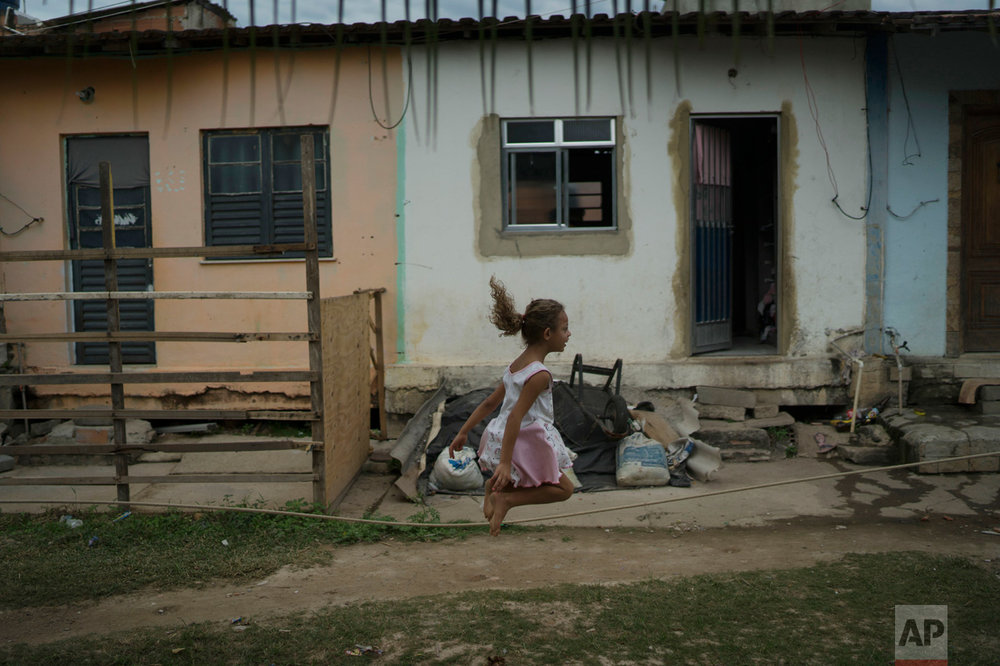 "In this June 8, 2017 photo, a girl jumps rope in the neighborhood of ""Cantinho do Ceu"" which means in Portuguese ""Heaven's corner,"" one of the poorest areas within the City of God slum in Rio de Janeiro, Brazil. (AP Photo/Leo Correa)"