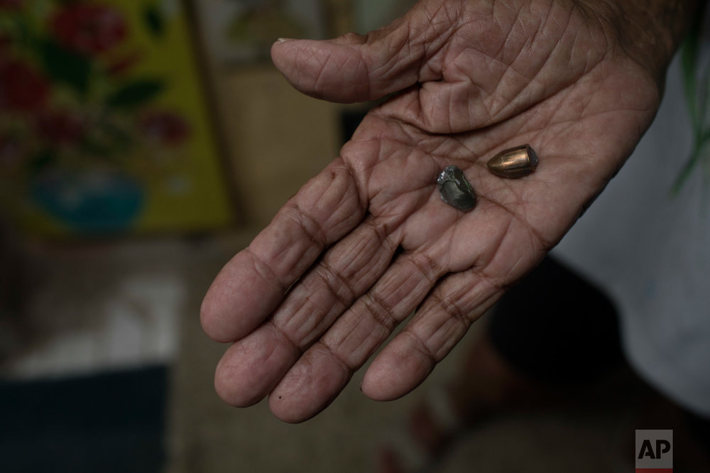 In this June 8, 2017 photo, artist Anayde dos Santos Muniz holds two bullets that recently hit her home near her bed in the City of God slum of Rio de Janeiro, Brazil. (AP Photo/Leo Correa)