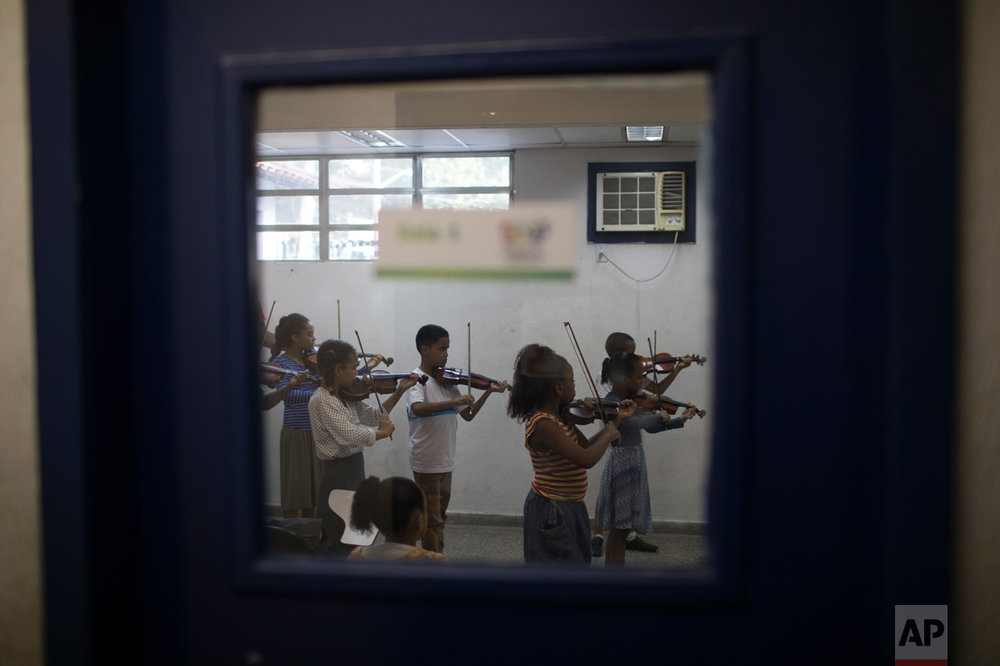In this June 7, 2017 photo, children take a violin class in the City of God slum of Rio de Janeiro, Brazil. Residents in Rio are dealing with the stress of an uptick in violence around them through art, recreation and helping each other. Teens participate in rap battles, others are learning a musical instrument or participating in capoeira circles. Still others do art or try to serve the most downtrodden among them, doing activities ranging from volunteering to cooking and offering free meals. (AP Photo/Leo Correa)