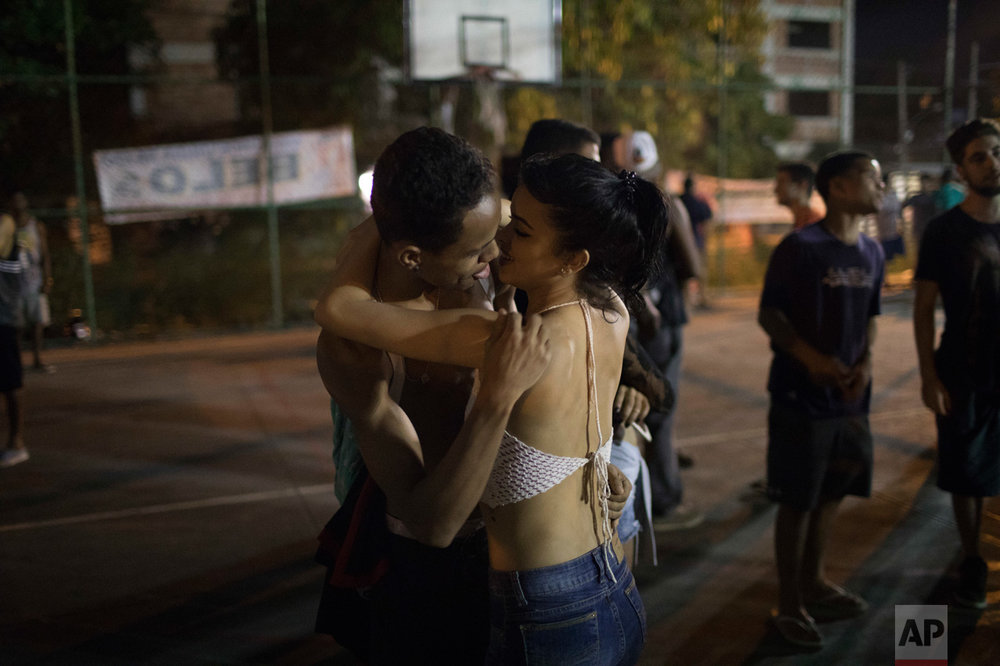 In this June 8, 2017 photo, a couple kiss on the sidelines of a night rap battle session in the City of God slum of Rio de Janeiro, Brazil. (AP Photo/Leo Correa)