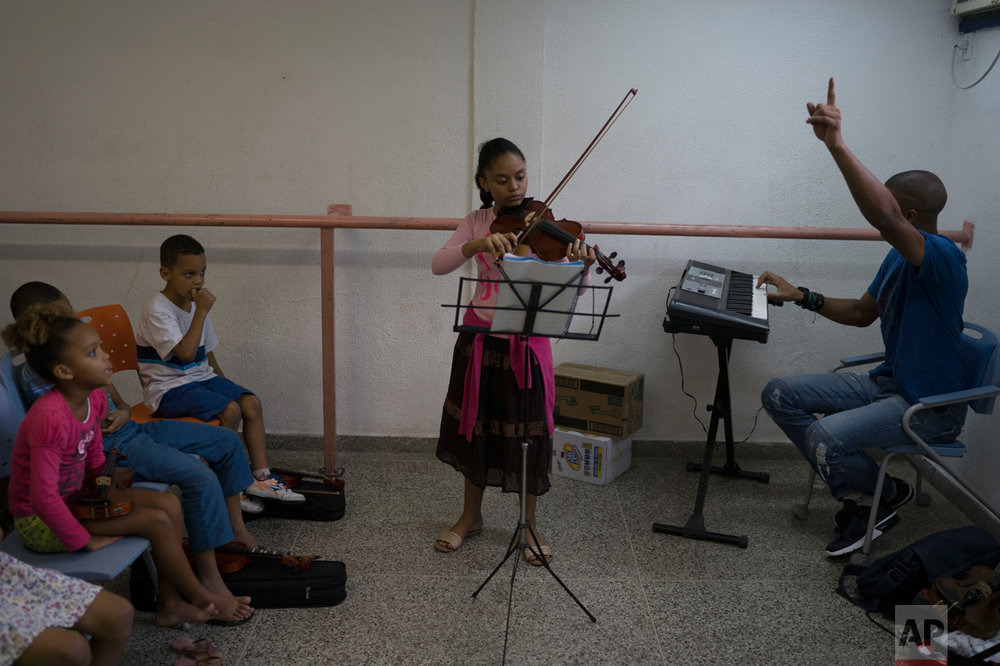 In this June 5, 2017 photo, Isabela Maia plays the violin during class in the City of God slum of Rio de Janeiro, Brazil. (AP Photo/Leo Correa)