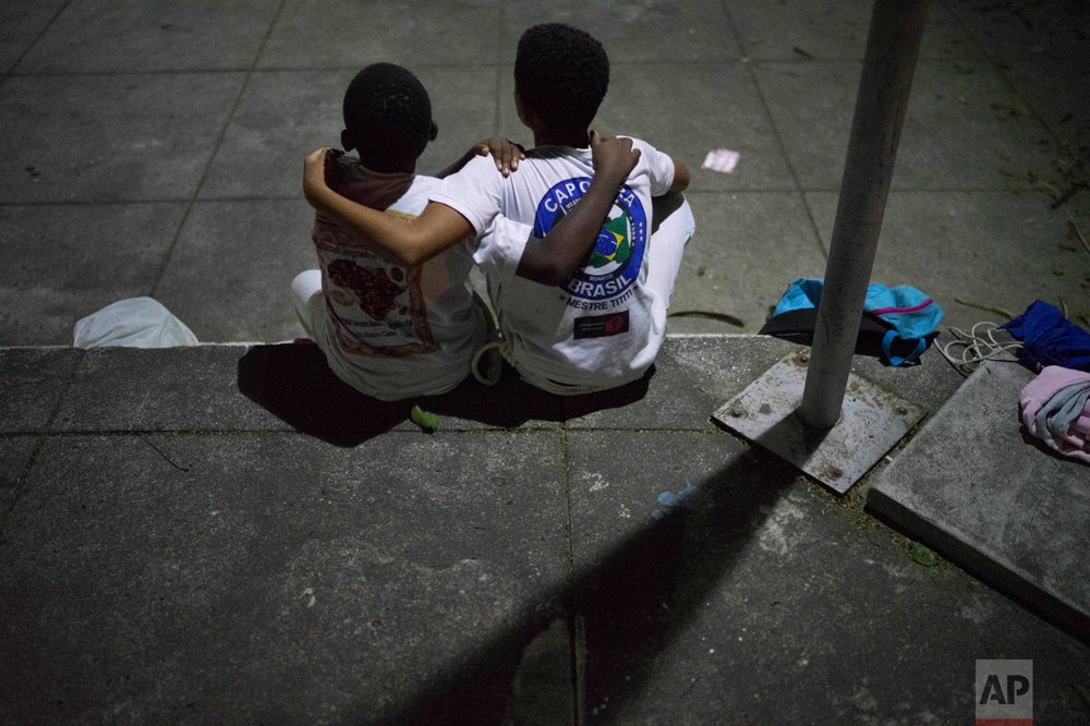 In this June 5, 2017 photo, boys embrace as they take a time-out from their Copeira class, assigned to them as a punishment for arguing, at a community center in the City of God slum in Rio de Janeiro, Brazil. (AP Photo/Leo Correa)