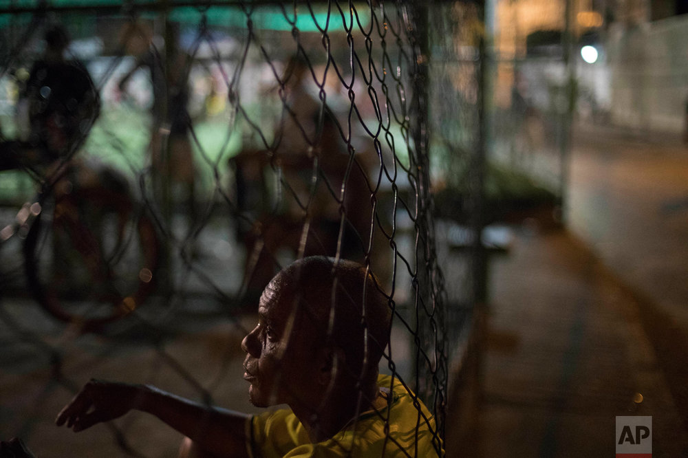 In this June 6, 2017 photo, rapper and breakdancing instructor Robson Luiz de Mendonca rests after playing basketball in the City of God slum of Rio de Janeiro, Brazil. (AP Photo/Leo Correa)