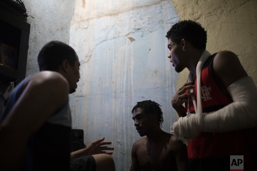 In this June 8, 2017 photo, Lucas dos Santos da Cruz, 18, center, talks with friends about the night's upcoming rap battle in the City of God slum of Rio de Janeiro, Brazil. (AP Photo/Leo Correa)