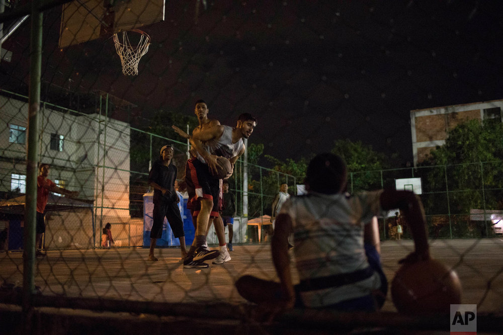 In this June 6, 2017 photo, youth play basketball in the City of God slum of Rio de Janeiro, Brazil. (AP Photo/Leo Correa)