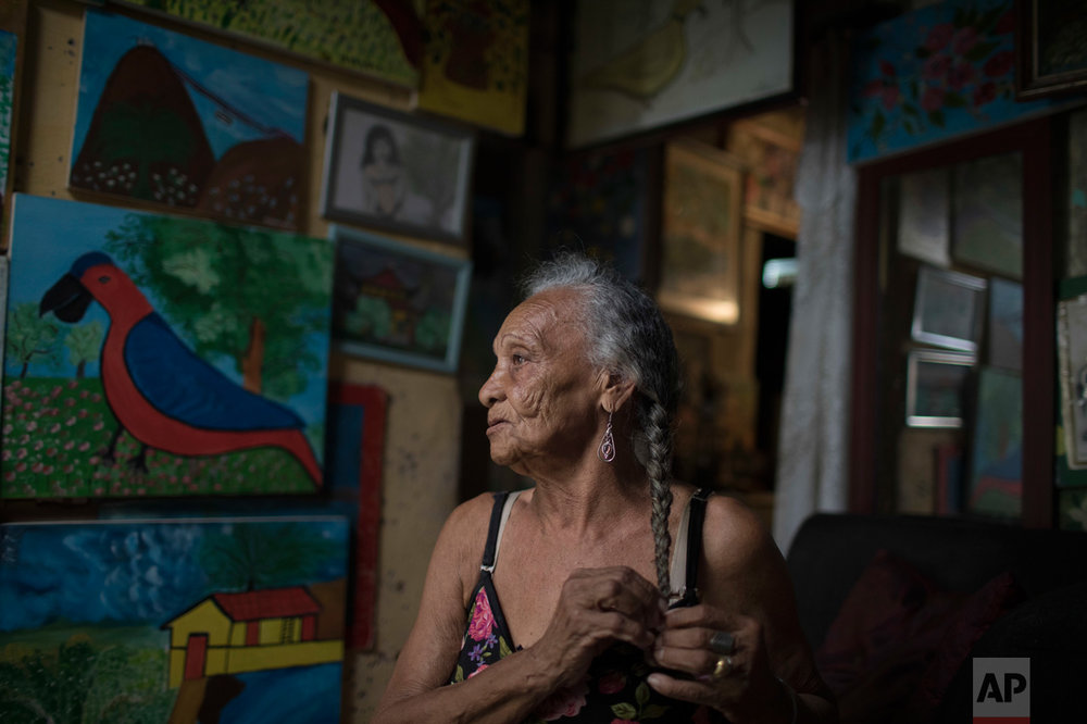 "In this June 9, 2017 photo, artist Anayde dos Santos Muniz, affectionately known as ""Tuca,"" poses for a portrait surrounded by her paintings inside her home in the City of God slum of Rio de Janeiro, Brazil. (AP Photo/Leo Correa)"