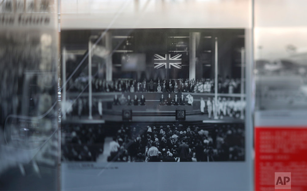 In this June 27, 2017, photo made with a tilt-shift lens, a photograph showing Chinese and British flags during the ceremony for the handover of Hong Kong to China on July 1, 1997, is displayed at an exhibition in Hong Kong. Two decades since Beijing took control of Hong Kong, China's rising influence – and Britain's waning profile – are impossible to ignore. (AP Photo/Vincent Yu)