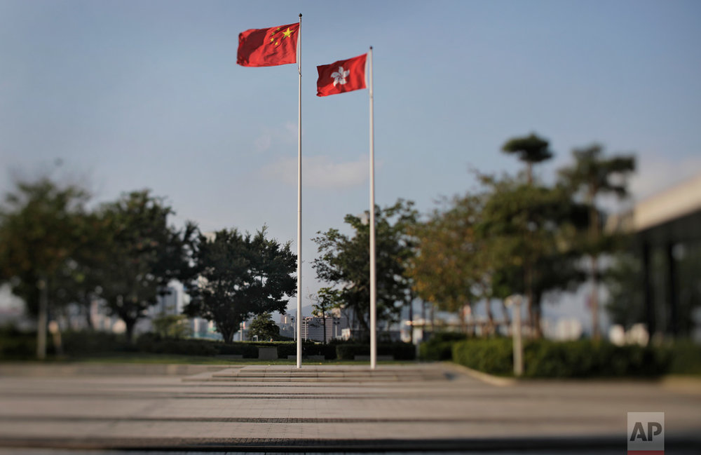 In this May 29, 2017, photo made with a tilt-shift lens, a Chinese national flag and a Hong Kong flag are flown at the Legislative Council, the legislature of Hong Kong. In Hong Kong's semi-democratic 70-seat Legislative Council, some lawmakers are directly elected and others represent business and professional groups, in a system that pro-democracy supporters complain lets Beijing maintain a disproportionate level of control. Two decades since Beijing took control of Hong Kong, China's rising influence – and Britain's waning profile – are impossible to ignore. (AP Photo/Vincent Yu)