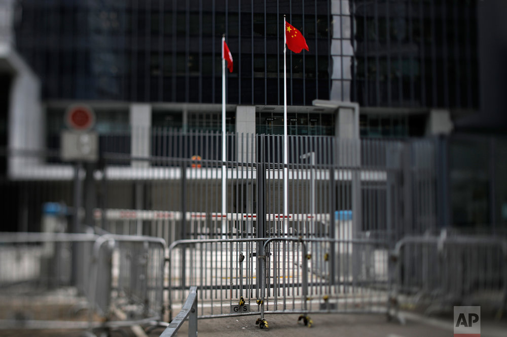 "In this June 8, 2017, photo made with a tilt-shift lens, a Chinese national flag and a Hong Kong flag are seen at the East Wing Forecourt of the Central Government Office in Hong Kong. The forecourt, known as Civic Square which is next to Hong Kong's city government headquarters, was fenced off in July 2014, angering activists who said the government had promised to let it be used for demonstrations. Student protesters rushed the courtyard in September 2014, sparking the 79-day ""Umbrella Movement"" protests. Two decades since Beijing took control of Hong Kong, China's rising influence – and Britain's waning profile – are impossible to ignore. (AP Photo/Vincent Yu)"