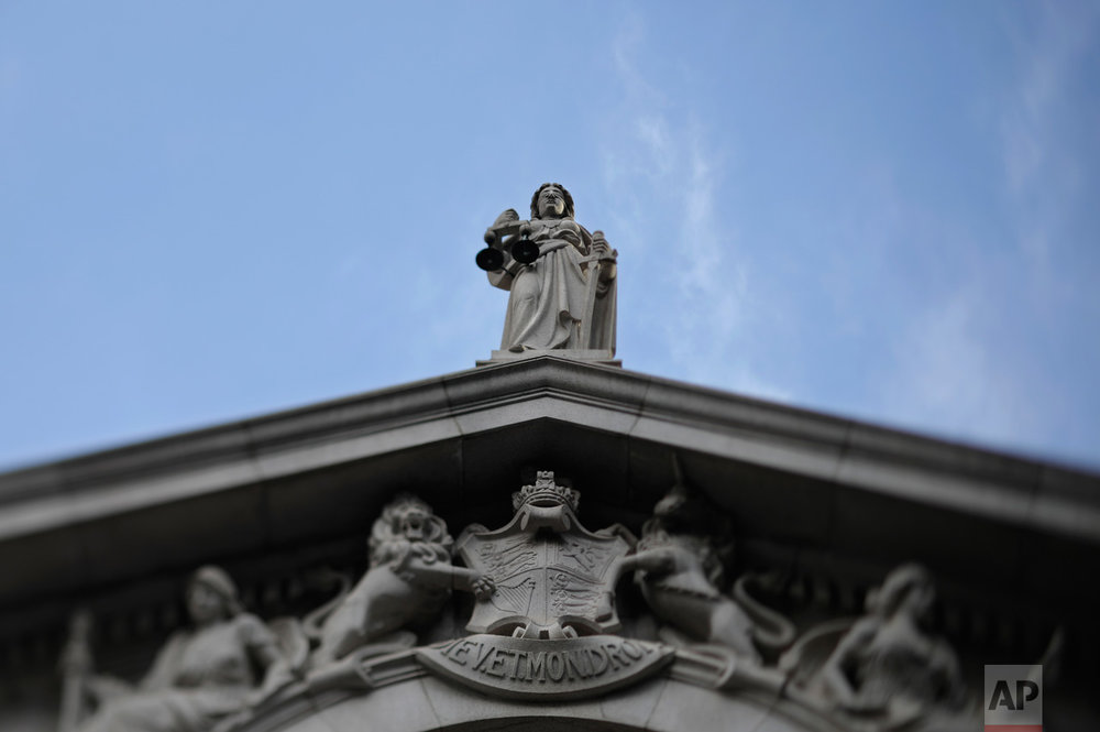 In this May 31, 2017, photo made with a tilt-shift lens, the blind-folded statue of the Greek goddess of justice and law is seen on top of the Court of Final Appeal in Hong Kong. (AP Photo/Vincent Yu)