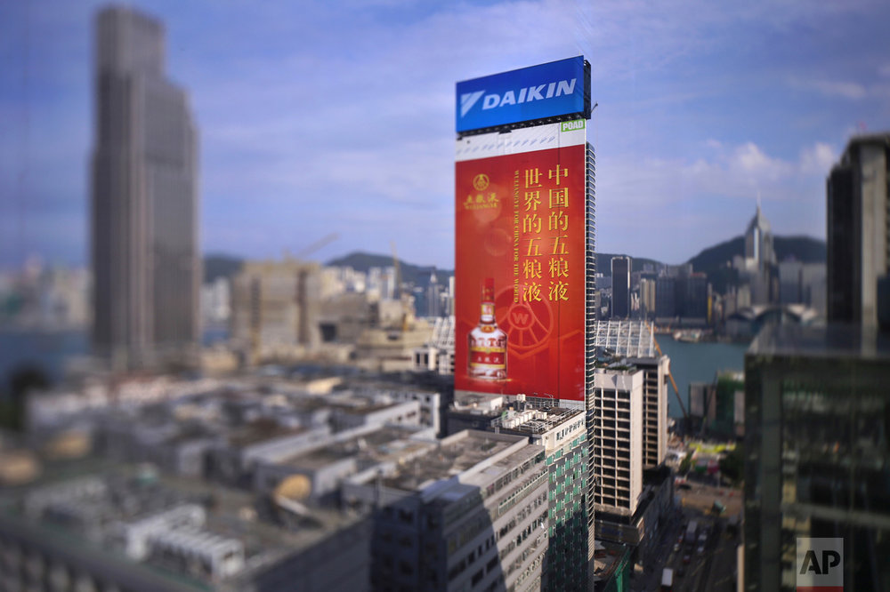 "In this May 27, 2017, photo made with a tilt-shift lens, an adverting board of China's best known spirit 'Wuliangye' is seen at the Tsim Sha Tsui district in Hong Kong. The Chinese words read ""Wuliangye for China for the world"". (AP Photo/Vincent Yu)"