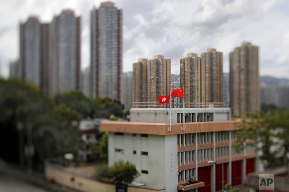 In this June 25, 2017, photo made with a tilt-shift lens, a Chinese national flag and a Hong Kong flag fly over a public housing estate in Hong Kong. Two decades since Beijing took control of Hong Kong, China's rising influence – and Britain's waning profile – are impossible to ignore. (AP Photo/Vincent Yu)