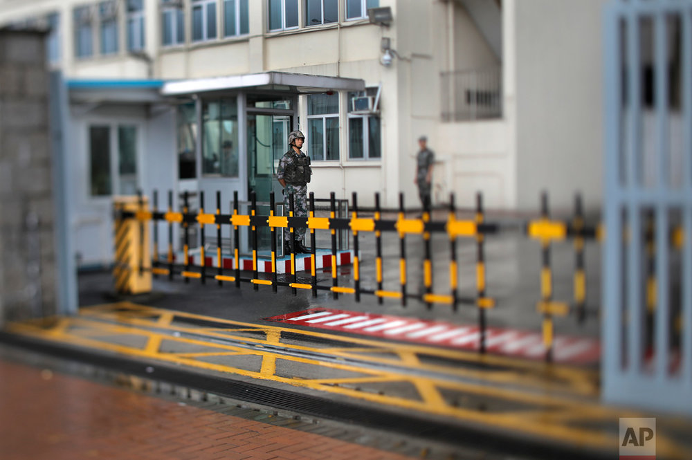 In this June 16, 2017, photo made with a tilt-shift lens, a Chinese soldier stands guard at the Chinese People's Liberation Army Forces building in Hong Kong. Hong Kong has no military of its own so its defense is left up to China's People's Liberation Army, which maintains a low key presence at a base near the city's financial district. (AP Photo/Vincent Yu)