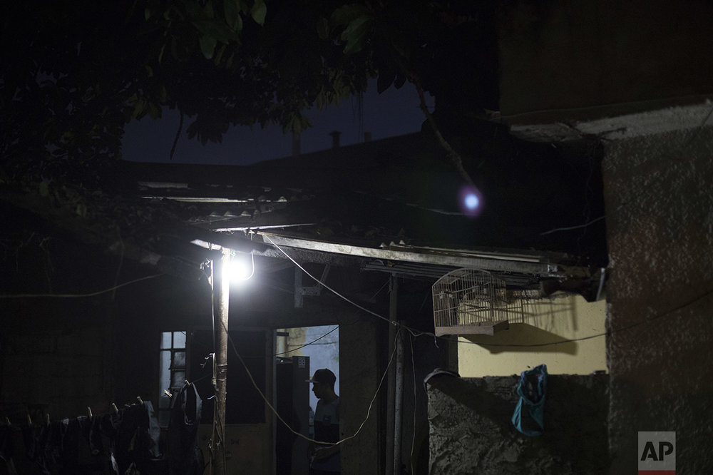 "In this June 8, 2017 photo, Erik Franca, 25, stands outside the room where he and his friends produce music in the City of God slum of Rio de Janeiro, Brazil. Soon after they left what they call ""the bunker,"" they went to a poorly illuminated square to compete in freestyle rap battles. (AP Photo/Leo Correa)"