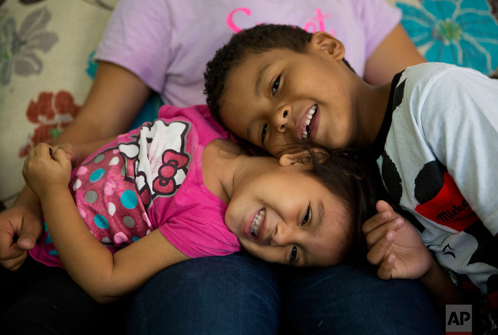 In this June 22, 2017 photo, Carlita Perez, 3, from El Salvador, and Josue Funez Cruz, 7, from Honduras, play together on the lap of Josue's sister Laura, 14, in the two-bedroom apartment the families share in the Iztapalapa district of Mexico City. (AP Photo/Rebecca Blackwell)