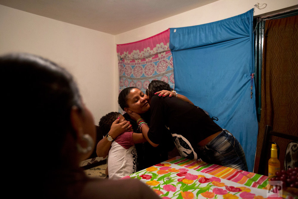 In this June 27, 2017 photo, Honduran refugee Laura Maria Cruz Martinez is hugged by her children Ruth, 12, right, and Josue, 7, after Ruth serenaded her with a song that thanks a single mother for the struggle and strength with which she raised her children, drawing tears from Laura, in the two-bedroom apartment they share with another refugee family in Mexico City.  (AP Photo/Rebecca Blackwell)