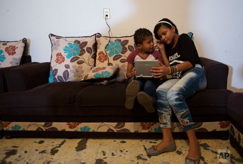 In this June 27, 2017 photo, Ruth Funez Cruz, 12, and her brother Josue, 7, try to watch a pirated DVD on a portable player with broken headphones, in the two-bedroom apartment they share with another refugee family in Mexico City. (AP Photo/Rebecca Blackwell)