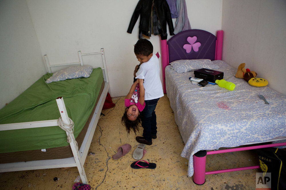 In this June 22, 2017 photo, Josue Funez Cruz, 7, from Honduras, carries Carlita Perez, 3, from El Salvador, as they play together in the two-bedroom apartment their families share in the Iztapalapa district of Mexico City. (AP Photo/Rebecca Blackwell)