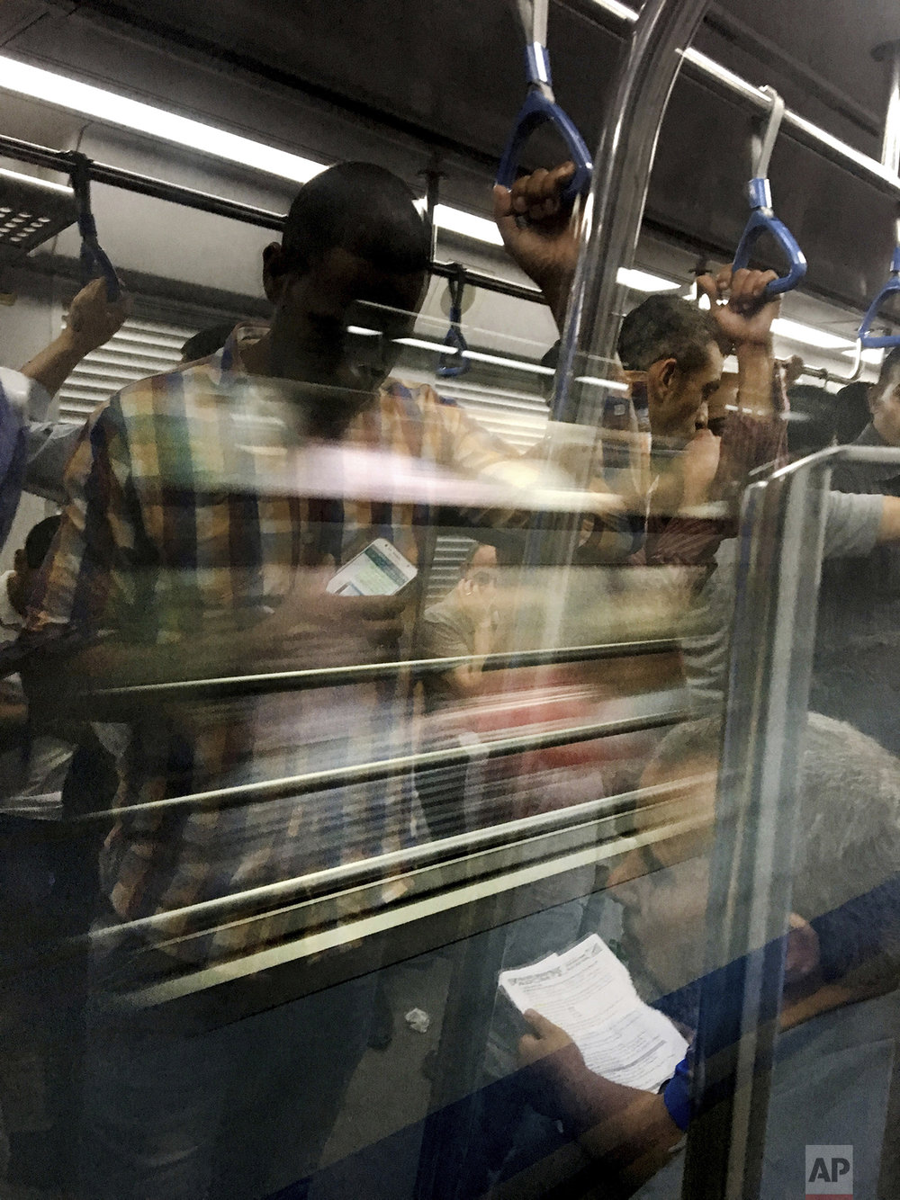 In this May 16, 2017 photo, commuters reflected in glass ride a metro car, in Cairo, Egypt. (AP Photo/Nariman El-Mofty)