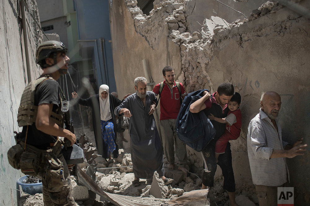 Iraqi civilians flee through a destroyed alley as Iraqi Special Forces move toward Islamic State positions in the Old City of Mosul, Iraq, Friday, June 30, 2017. (AP Photo/Felipe Dana)