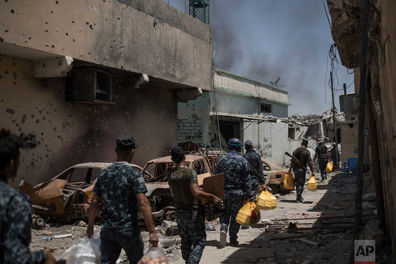 Federal policemen carry food to the frontline during fighting against Islamic State militants in the Old City of Mosul, Iraq, Monday, June 26, 2017. Islamic State fighters launched a string of counterattacks in a western Mosul neighborhood that had recently been declared free of the militant group, setting off clashes that continued overnight, Iraqi officials said Monday. (AP Photo/Felipe Dana)