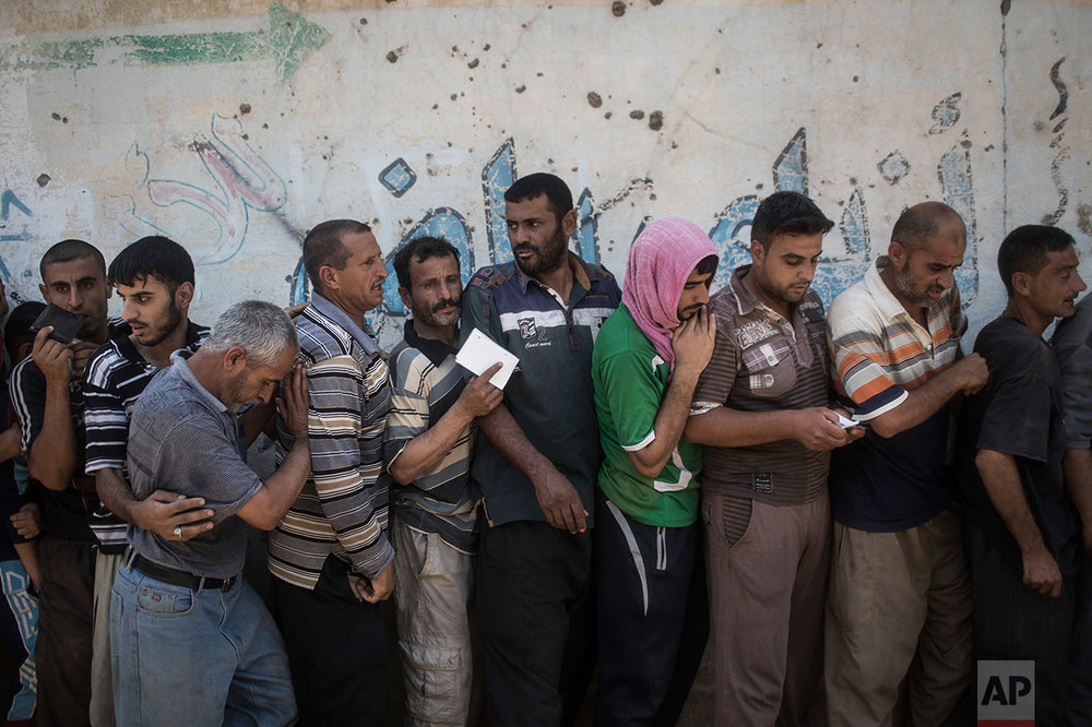 Civilians gather at a food distribution point in a neighborhood recently liberated by Iraqi security forces during fighting against Islamic State militants in Mosul, Iraq, Saturday, June 24, 2017. (AP Photo/Felipe Dana)