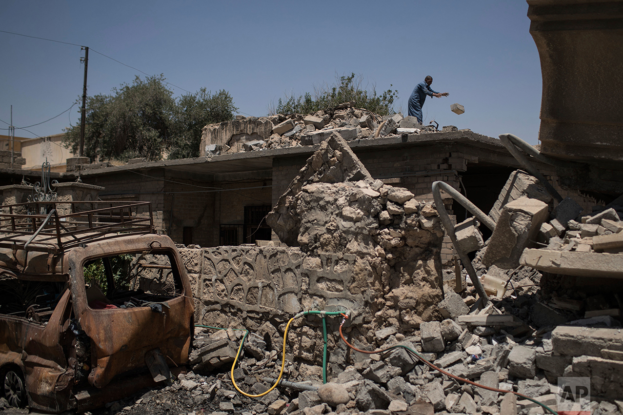 An Iraqi man removes rubble from his damaged house in a neighborhood recently retaken by Iraqi security forces during fights against Islamic State militants in Mosul, Iraq, Friday, June 23, 2017. Formally launched in October, the fight for Mosul has displaced more than 850,000 people. (AP Photo/Felipe Dana)