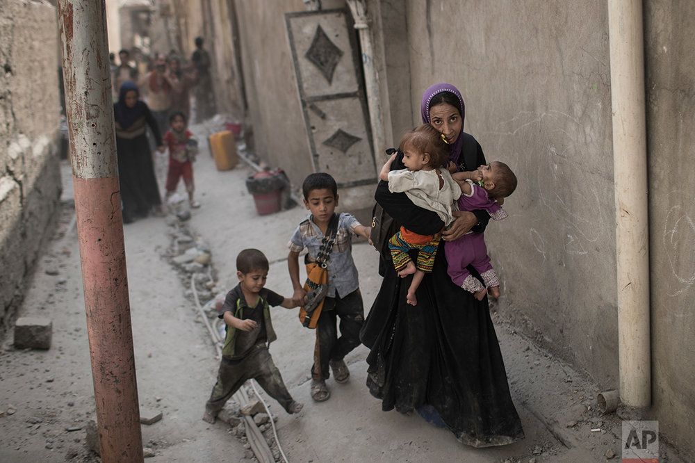 Iraqi civilians flee through an alley as Iraqi Special Forces continue their advance against Islamic State militants in the Old City of Mosul, Iraq, Monday, July 3, 2017. (AP Photo/Felipe Dana)