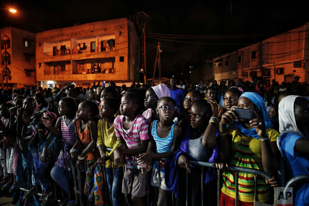 Senegalese youth watch a runway show during Dakar Fashion Week in the capital's Niari Tali neighborhood, Thursday June 29, 2017. (AP Photo/Finbarr O'Reilly)