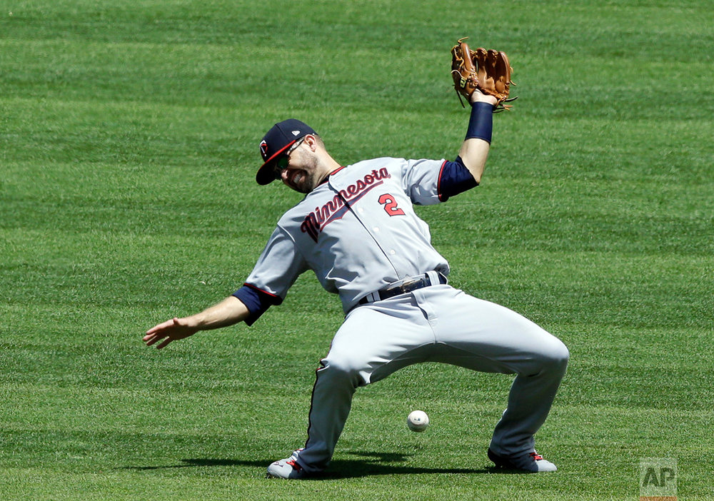 Minnesota Twins' Brian Dozier can't make the catch on a single hit by Cleveland Indians' Lonnie Chisenhall in the second inning of a baseball game, Sunday, June 25, 2017, in Cleveland. (AP Photo/Tony Dejak)