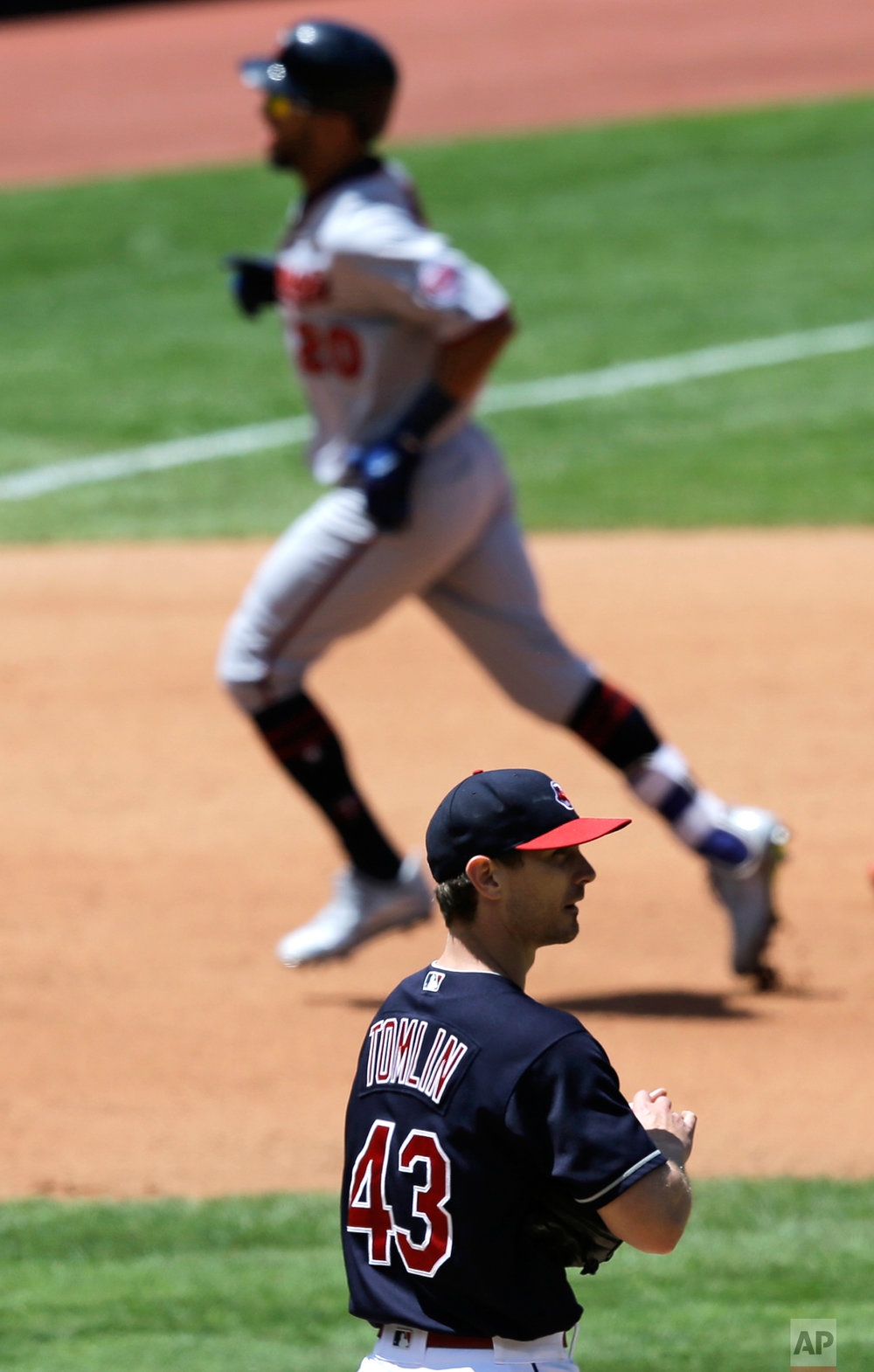 Cleveland Indians starting pitcher Josh Tomlin (43) waits for Minnesota Twins' Eddie Rosario, top, to run the bases after Rosario hit a solo home run in the fourth inning of a baseball game, Sunday, June 25, 2017, in Cleveland. (AP Photo/Tony Dejak)