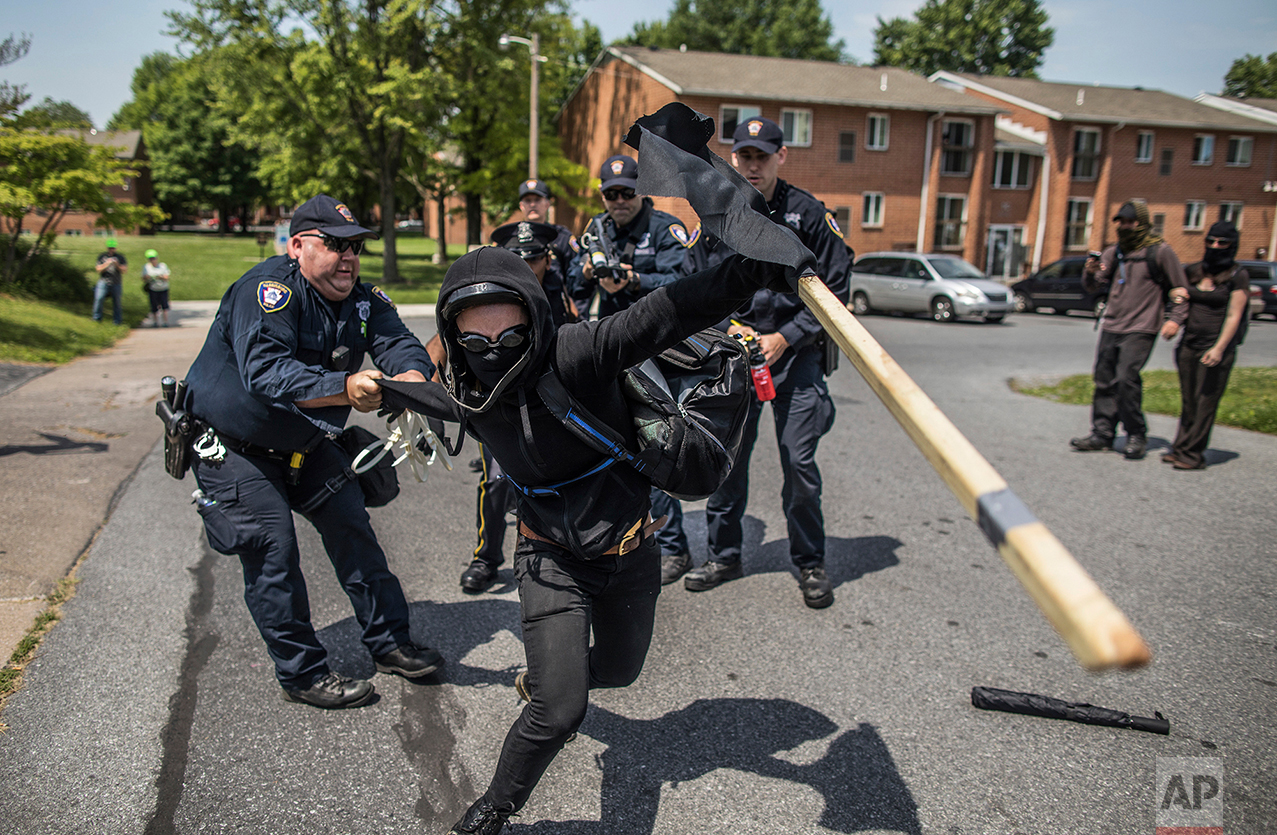A police officer tries to hold onto a member of a counter-protest group against anti-Shariah protesters in Harrisburg, Pa., Saturday, June 10, 2017. Demonstrators at small but raucous gatherings around the country Saturday raised the specter that extremist interpretations of Islamic law might somehow spread across the U.S., but many of the rallies drew even more boisterous counter-protests by people who called such fears unfounded. (Sean Simmers/PennLive.com via AP)