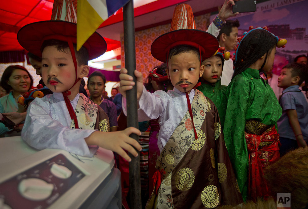 Tibetan children watch others dance as they wait for their turn to perform during celebrations marking the 82nd birthday of their spiritual leader, the Dalai Lama, at a Tibetan settlement in New Delhi, India, Thursday, July 6, 2017. (AP Photo/Manish Swarup)