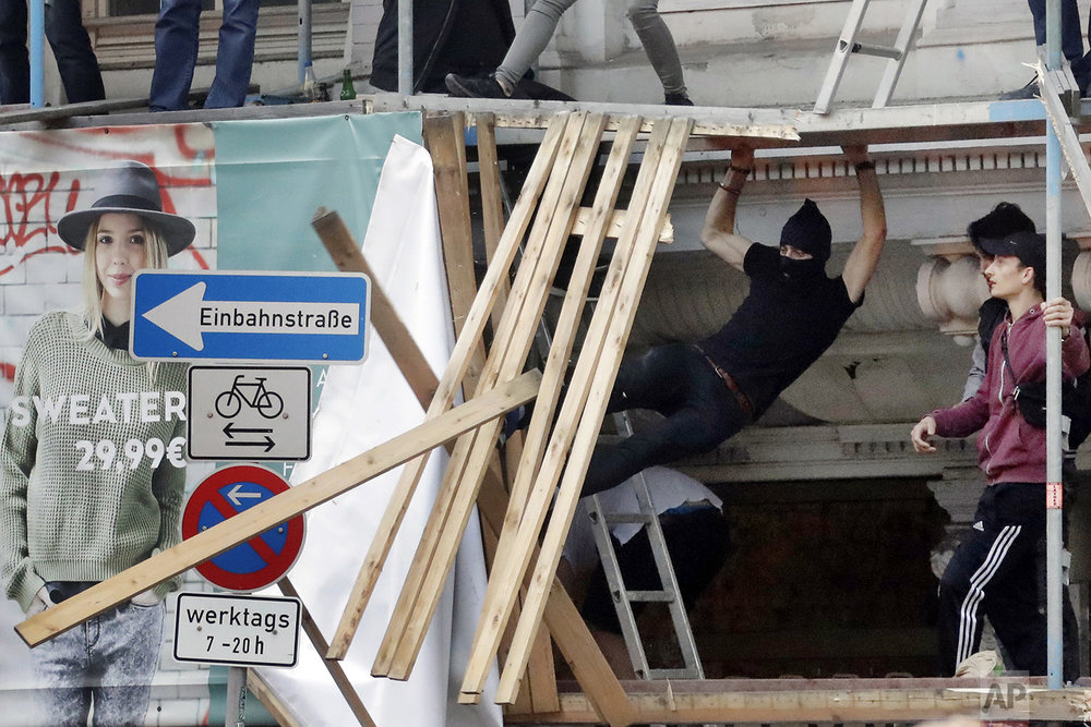 A masked man kicks wooden boards from a scaffold during a protest against the G-20 summit in Hamburg, northern Germany, Friday, July 7, 2017. (AP Photo/Matthias Schrader)