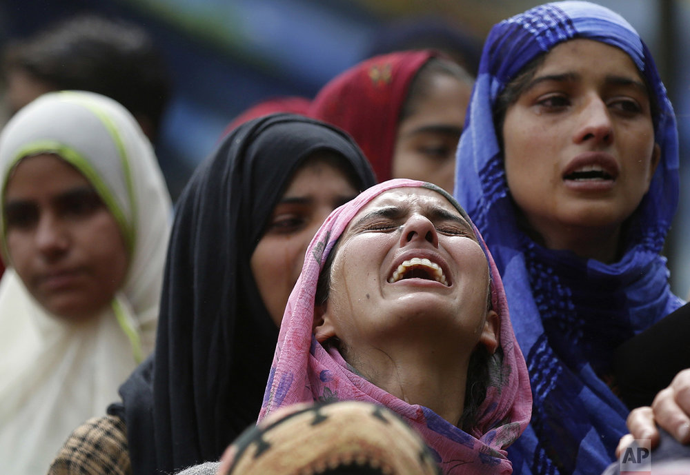 A relative cries near the body of killed rebel Jehinger Ahmad during his funeral at Keller, 49 kilometers (30 miles) south of Srinagar, Indian controlled Kashmir, Tuesday, July 4, 2017. (AP Photo/Mukhtar Khan)