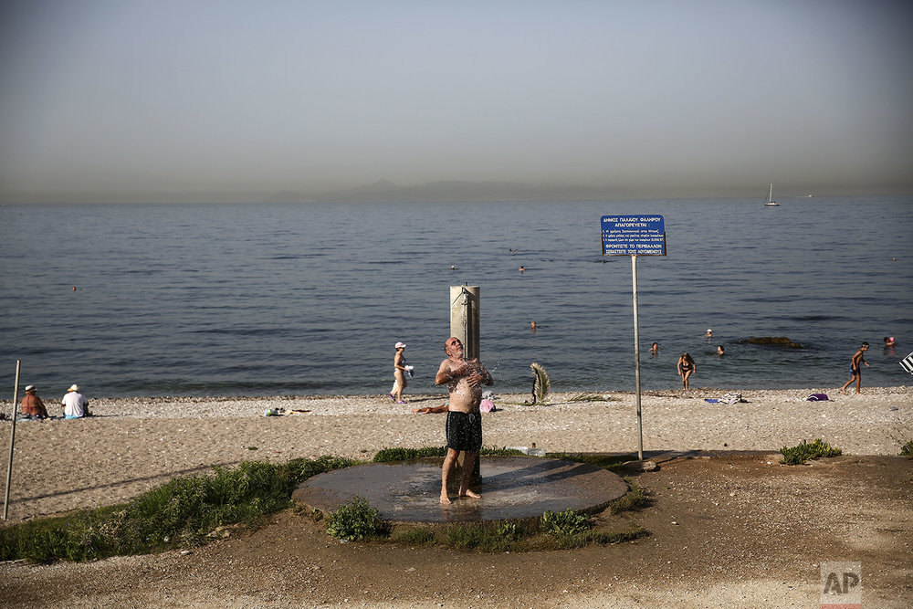 A man takes a shower at a beach of Alimos suburb in Athens, on Saturday, July 1, 2017. (AP Photo/Yorgos Karahalis)