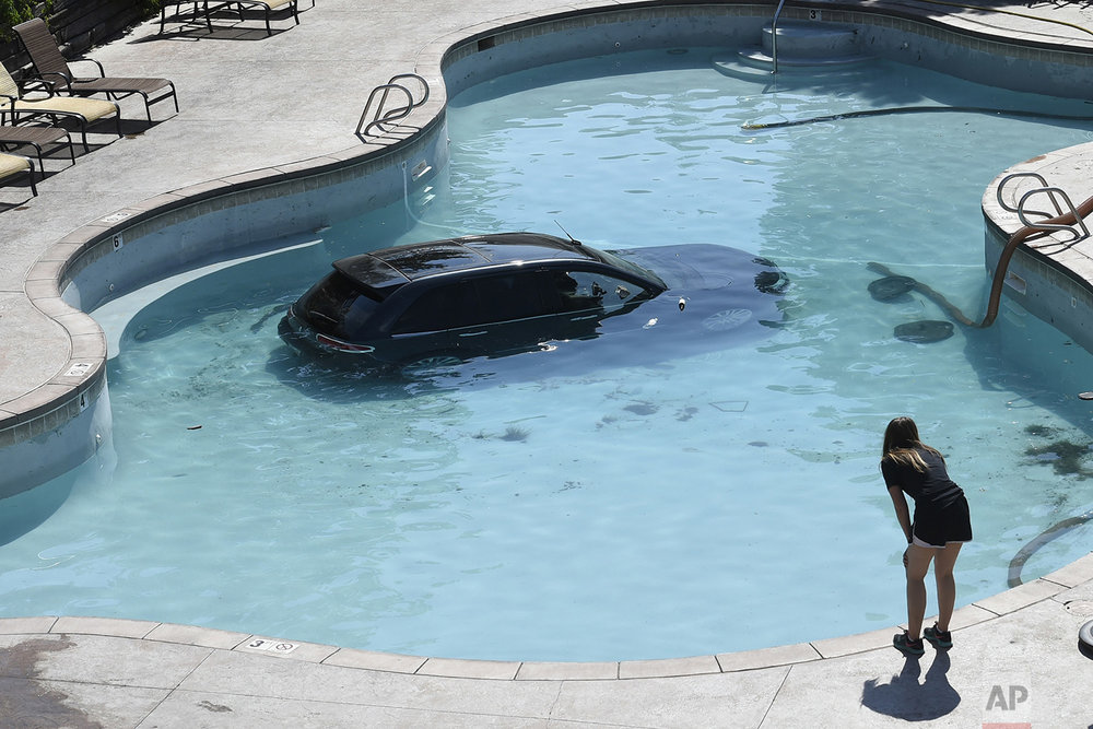 Water from a pool is pumped out before a vehicle is towed at the Cheyenne Mountain Resort in Colorado Springs, Colo., Monday, July 3, 2017. (Jerilee Bennett/The Gazette via AP)